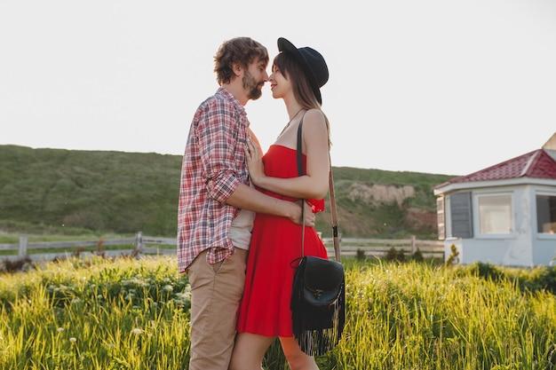 田舎、インディーヒップスターボヘミアンスタイル、週末の休暇、夏の服装、赤いドレスの恋のスタイリッシュなカップルを抱きしめる日当たりの良いキス