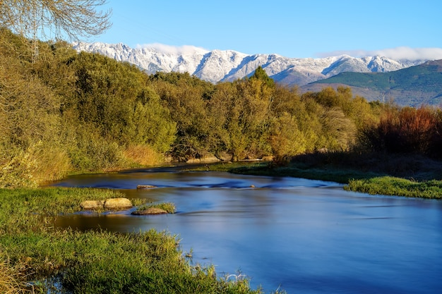 Sunny landscape with rays of sun, river with water and grass in winter sunrise. gredos, avila.