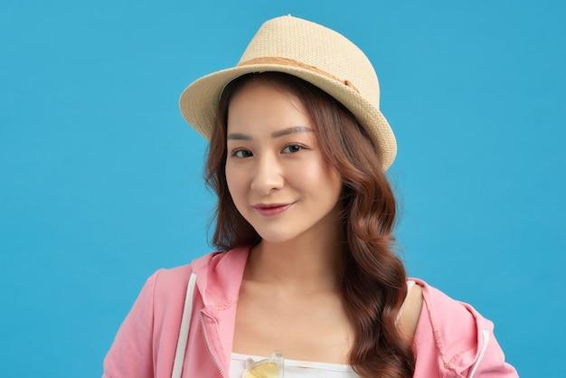 トレンディな衣装、麦わら帽子を身に着けている若い女性の日当たりの良いライフスタイルファッションの肖像画