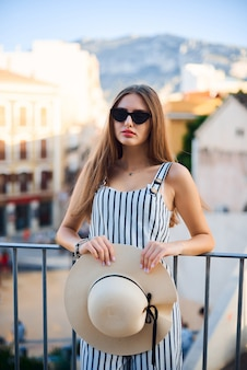 Sunny lifestyle fashion portrait of young stylish woman walking on the street.