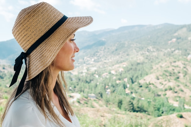 Sunny lifestyle portrait of young hipster woman, wearing straw hat. portrait with valley landscape