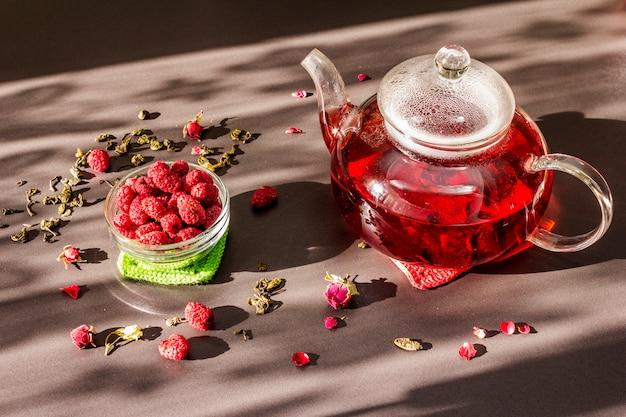Солнечное утро, завтрак. сладкий малиново-зеленый чай в стеклянном чайнике с сухими фруктами, цветами и листьями