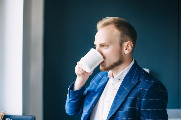Sunny morning a young businessman drinks coffee in an office european man in a blue jacket