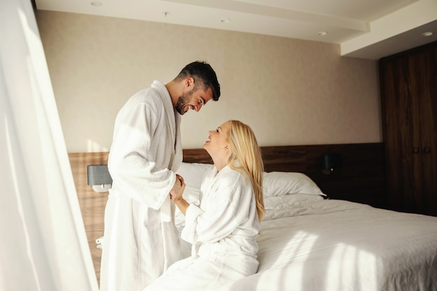 Sunny mornings in a room of a modern hotel, close couple in white bathrobes share a moment to remember