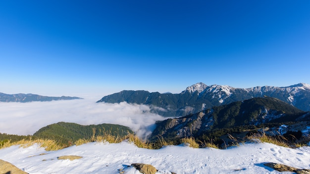 Sunny mountain view of snow covered alps with trees and clouds in the valley