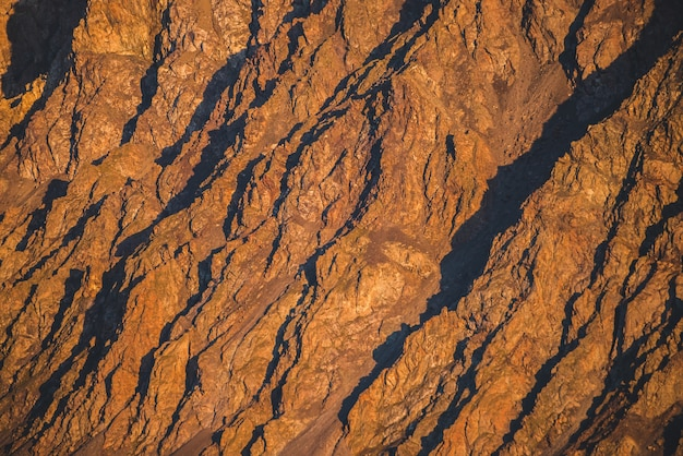 Sunny nature background of rockies in sunlight. vivid natural mountain texture of big rough rocks. full frame of bright giant craggy surface. rocky mountain close-up. plane of shiny rocks on sunset.