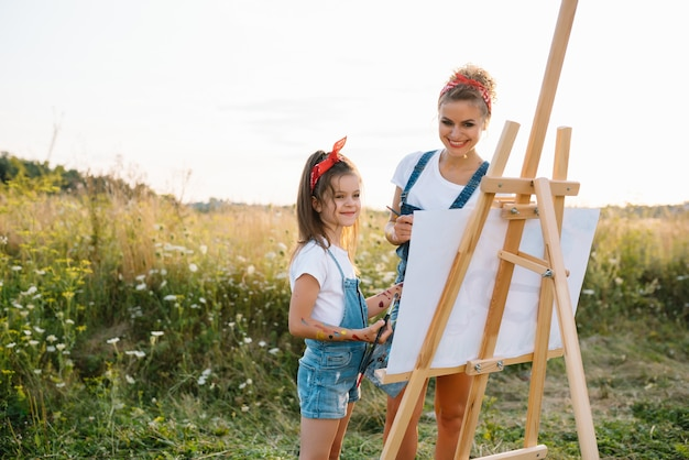 Sunny nature, mom and daughter paint a picture in a park , painting a little child, child creativity.