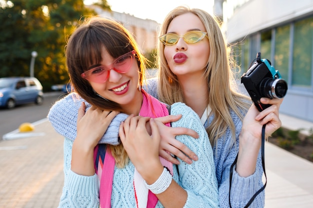 Sunny outdoor portrait or two cheerful funny hipster woman making selfie on vintage camera wearing pastel colors trendy sweaters and glasses, sister best friends having fun together.