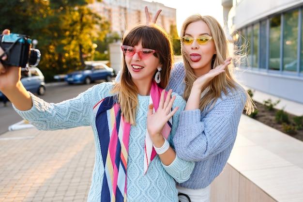 Ritratto all'aperto soleggiato o due donna allegra e divertente hipster che fa selfie sulla macchina fotografica d'epoca indossando maglioni e occhiali alla moda di colori pastello, migliori amiche della sorella che si divertono insieme.