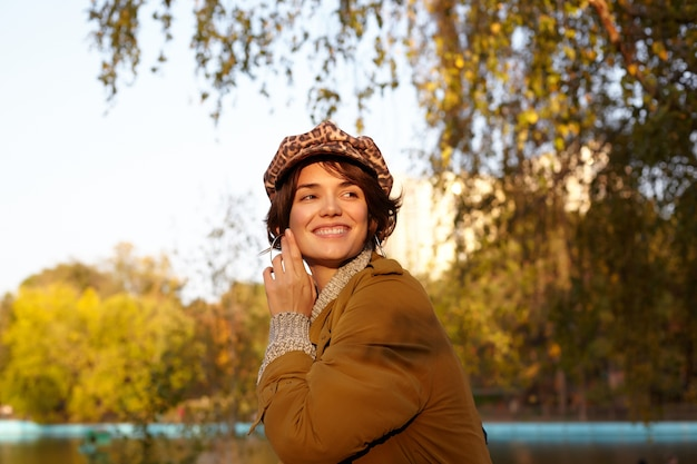Sunny photo of cheerful young lovely short haired brunette woman smiling pleasantly while looking aside and touching gently her face with raised hand, posing outdoor on warm autumn day