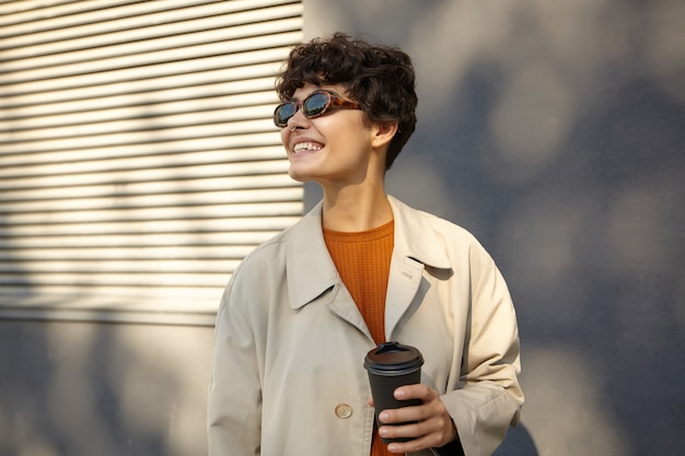 Sunny photo of pretty young brunette curly female with casual hairstyle keeping black paper cup in raised hand and looking aside cheerfully with wide smile, dressed in trendy outfit