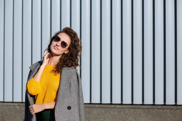 Sunny portrait of attractive hipster girl walking down the street, wearing trendy outfit. space for text