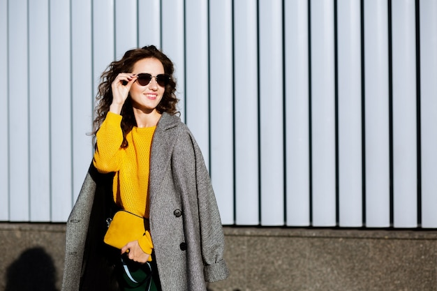 Sunny portrait of beautiful happy woman walking down the street,wearing trendy outfit. space for text