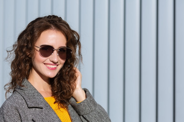 Sunny portrait of cheerful hipster girl walking down the street,wearing trendy outfit. space for text
