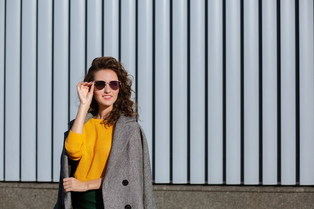 Sunny portrait of elegant hipster girl walking down the street,wearing trendy outfit. space for text