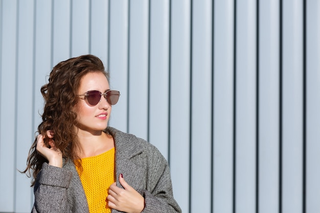 Sunny portrait of gorgeous hipster girl walking down the street,wearing trendy outfit. space for text