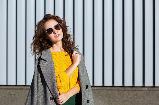 Sunny portrait of lovely hipster girl walking down the street, posing near the shutters. space for text