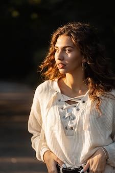 해질녘 공원에 있는 세련된 니트 스웨터에 예쁜 얼굴과 곱슬머리를 한 아름다운 젊은 여성의 맑은 초상화. 자연 여성의 아름다움