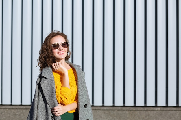 Sunny portrait of pretty hipster girl walking down the street,wearing trendy outfit. space for text