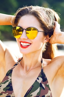Sunny portrait of pretty woman on sunlight, bright colors and fashion mood, fitness strong body, summer vacation.