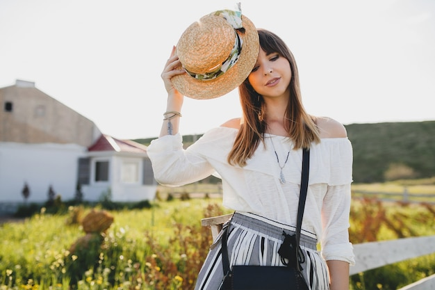 Sunny portrait of smiling young beautiful stylish woman, spring summer fashion trend, boho style, straw hat, countryside weekend, sunny, black purse