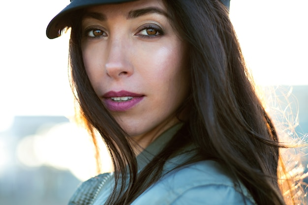 Sunny portrait of stunning young woman, long brunette hairs, trendy hat nd jacket, cold spring autumn time.