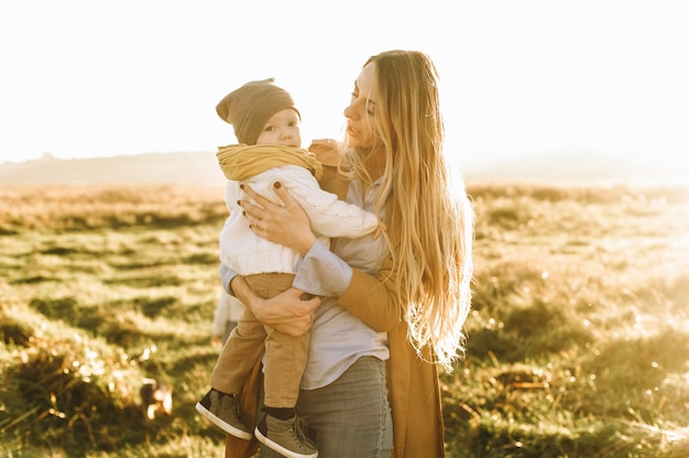 Sunny portraits of mom and her son at sunset