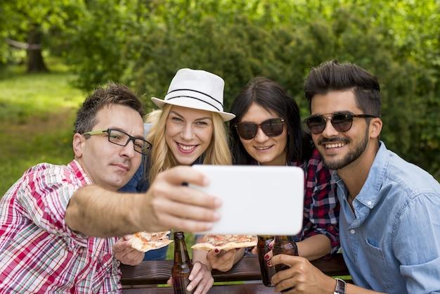 Scenario soleggiato di un gruppo di amici caucasici che brindano con le loro bottiglie di birra in un parco