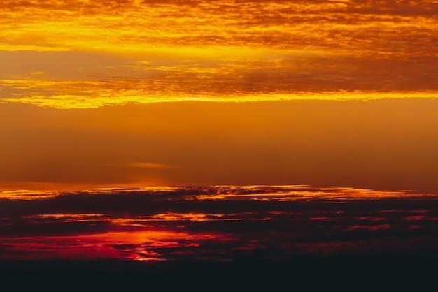 Солнечный блеск на облаках. прекрасный яркий рассвет. красивый спокойный оранжевый закат. живописный сюрреалистический восход. удивительное красное облачное небо. живописный закат. атмосферные облака. круг солнца над горизонтом.