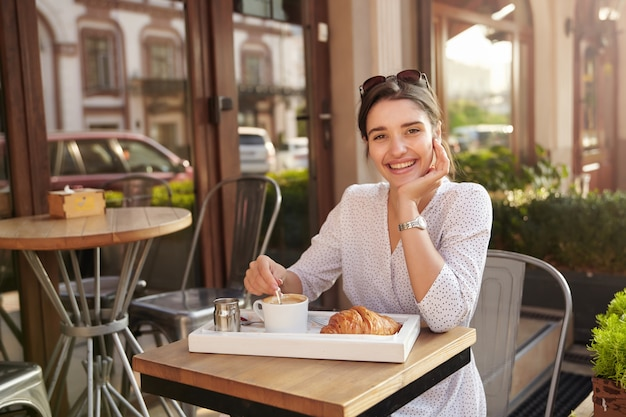 Sunny shot of cheerful young lovely dark haired female in white polka-dot wear sitting at table in city cafe, leaning her chin on raised hand and smiling happily