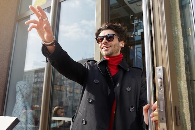 Colpo soleggiato di giovane ragazzo barbuto dai capelli castani attraente in abiti alla moda che esce dal caffè e incontra gli amici, alzando la mano in gesto di ciao e sorridendo felice