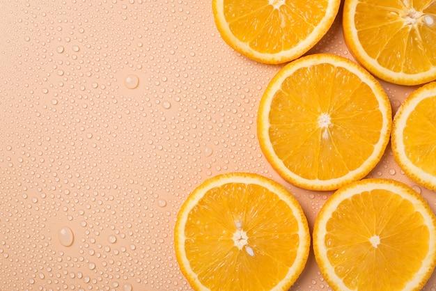 晴れた夏のコンセプト。頭上の上のクローズアップは、テキストコピーの空白の空きスペースの場所と水滴とテーブルの上のジューシーなオレンジスライスの写真を表示