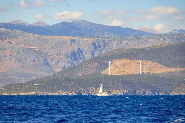 Солнечный летний день и холмистое побережье с ветряными электростанциями. одинокая парусная яхта