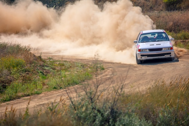 Sunny summer day. dusty rally track. sports car does a lot of dust in turn 01
