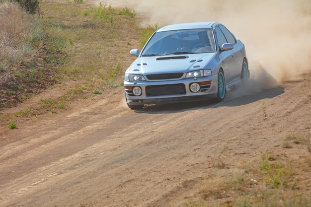 Sunny summer day. dusty rally track. sports car does a lot of dust in turn 02