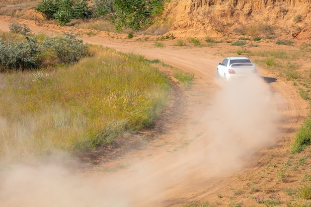 Sunny summer day. dusty rally track. sports car does a lot of dust in turn 03