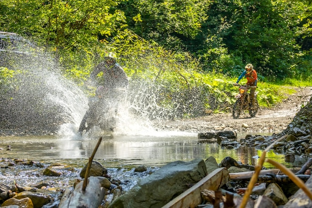 Sunny summer day in the forest. two enduro athletes overcomes a shallow stream with lots of water splashes