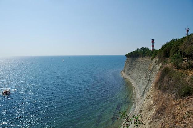 晴れた夏の日。古い灯台黒い海の岩の多い海岸