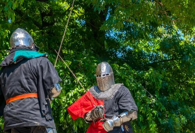 Солнечный летний день. два средневековых солдата в доспехах и железных шлемах сражаются на мечах