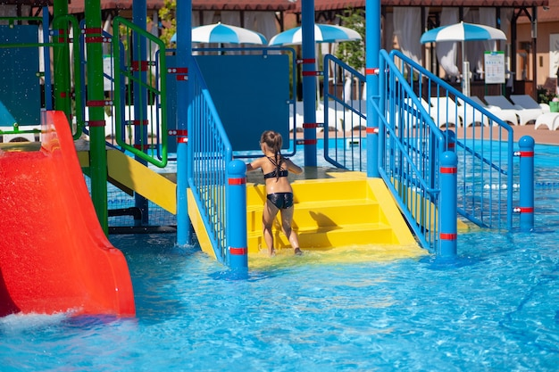 Sunny summer day at water park little girl enjoys holidays and recreation in pool of entertainment c...