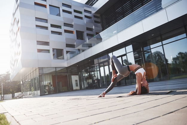 Sunny summer morning. young athletic woman doing handstand on city park street among modern urban buildings. exercise outdoors healthy lifestyle