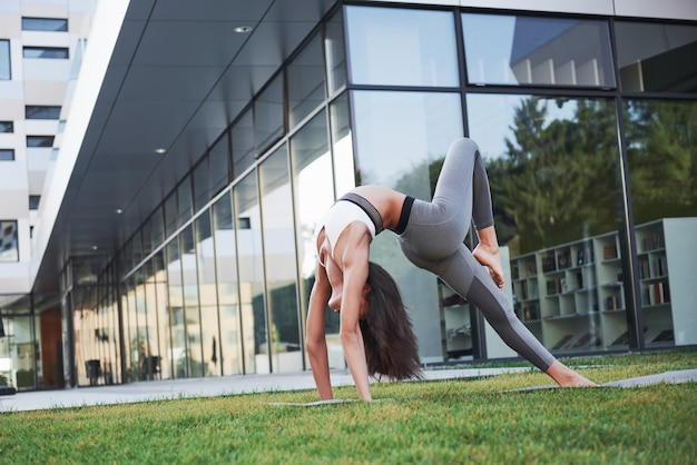 Sunny summer morning. young athletic woman doing handstand on city park street among modern urban buildings. exercise outdoors healthy lifestyle.