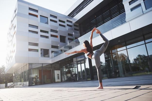 화창한 여름 아침입니다. 현대 도시 건물 중 도시 공원 거리에 손으로 하 고 젊은 운동 여자. 야외 건강 운동
