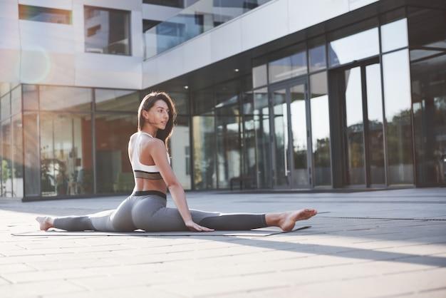 Солнечное летнее утро. молодая атлетическая женщина делая стойку на руках на улице парка города среди современных городских зданий. физические упражнения на свежем воздухе