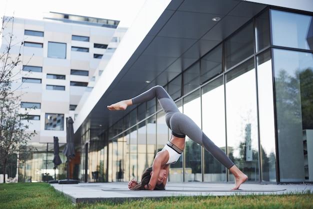 Солнечное летнее утро. молодая спортивная женщина делает стойку на руках на улице городского парка среди современных городских зданий. занятия спортом на открытом воздухе здорового образа жизни.