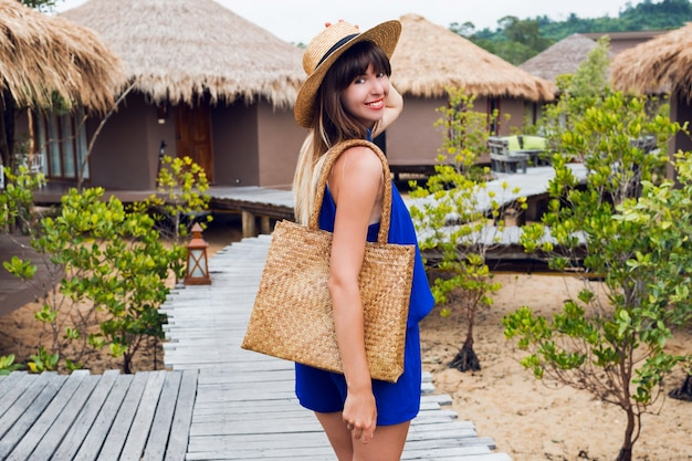 Sunny summer portrait of cute brunette woman in straw hat and trendy boho bag walking in tropical villa in thailand.