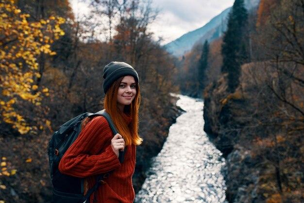 Солнечный турист у реки горы осенний лесной пейзаж