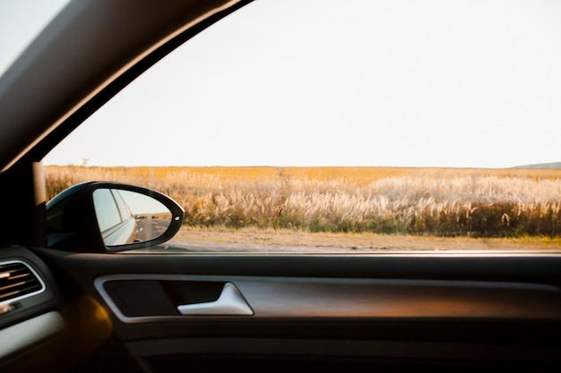 Sunny view on a field from elegant car
