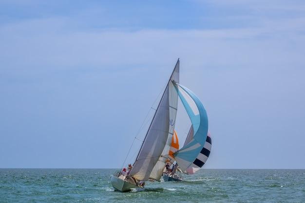 넓은 바다의 화창한 날씨. 상당한 기울기로 가는 스피너커가 있는 세 개의 세일링 요트