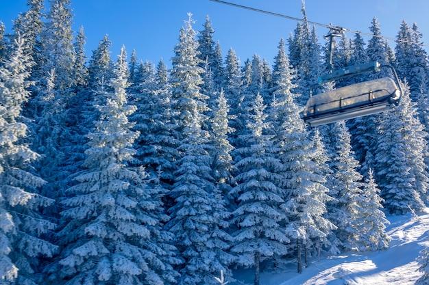 冬の森の晴天。雪に覆われたモミの木を背景にしたチェアスキーリフトのキャビン